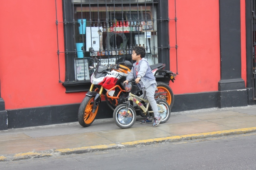 Child sizes up motorcycle in Lima, Peru
